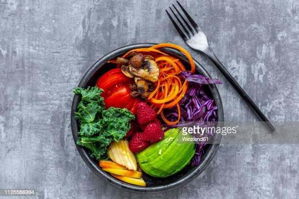 kale avocado salad with red cabbage, tomato, fried mushroom, carrot, apple and raspberry - cabbage family stock photos and pictures