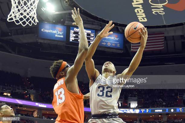 Kaleb Johnson of the Georgetown Hoyas takes a shot over Paschal Chukwu of the Syracuse Orange during a college basketball game at Capitol One Arena...