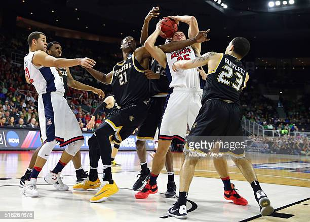 Kaleb Tarczewski of the Arizona Wildcats and Bush Wamukota of the Wichita State Shockers battle for a rebound during the first round of the 2016 NCAA...