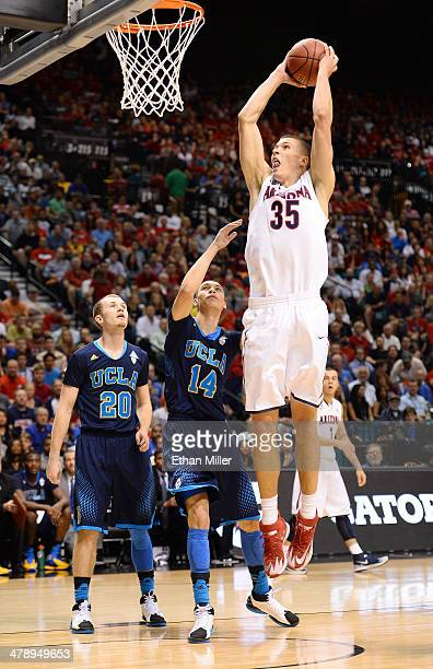 Kaleb Tarczewski of the Arizona Wildcats goes in for a dunk against Bryce Alford and Zach LaVine of the UCLA Bruins during the championship game of...