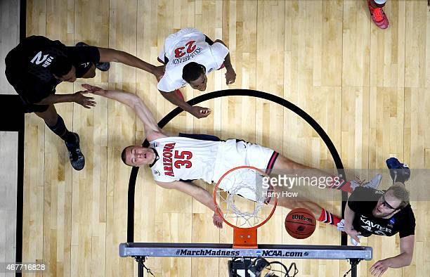 Kaleb Tarczewski of the Arizona Wildcats lays on the court alongside Matt Stainbrook of the Xavier Musketeers during the West Regional Semifinal of...