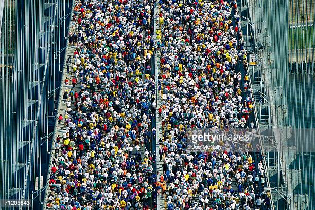 A kaleidoscopic crowd of 30000 runners surges across the VerrazanoNarrows Bridge during the New York City Marathon on November 7 1999 in New York...