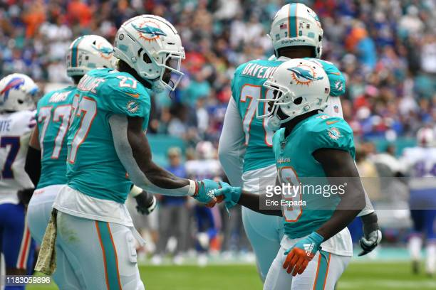 Kalen Ballage of the Miami Dolphins celebrates with Jakeem Grant after scoring a touchdown in the second quarter against the Buffalo Bills at Hard...