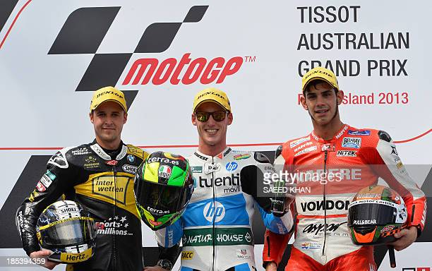 Kalex rider Pol Espargaro of Spain celebrates his victory along with secondplaced Suter rider Thomas Luthi of Switzerland and thirdplaced Suter rider...