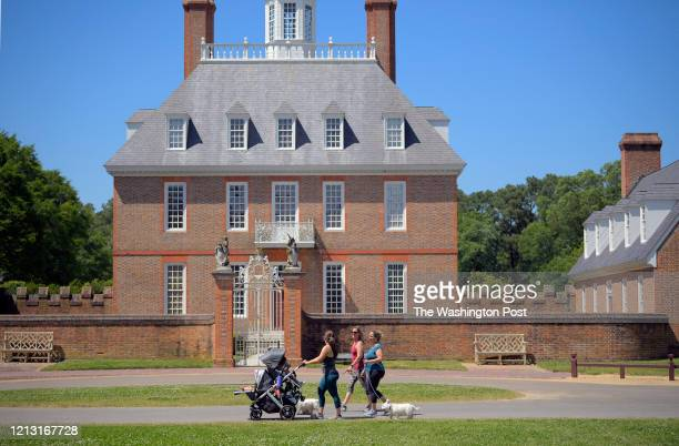 Kaley Campana, left, Anne Pinto, center, and Jennifer Hudgins stroll by the Governors Palace in a near empty Colonial Williamsburg that will open...
