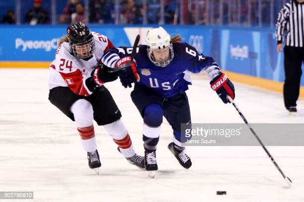 Kali Flanagan of the United States controls the puck against Natalie Spooner of Canada in overtime during the Women's Gold Medal Game on day thirteen...