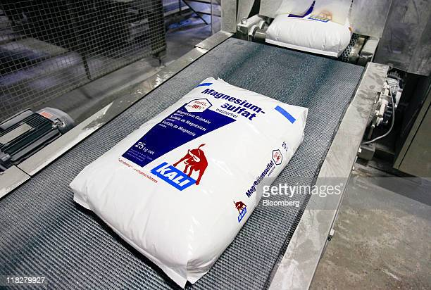 KS Kali GmbH branded sacks of magnesium sulfate commonly called Epsom salts pass along a conveyor belt at the company's warehouse in Bebra Germany on...