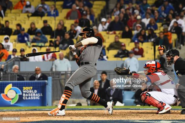 Kalian Sams of the Netherlands shatters his bat at the plate in the ninth inning against team Puerto Rico during Game 1 of the Championship Round of...
