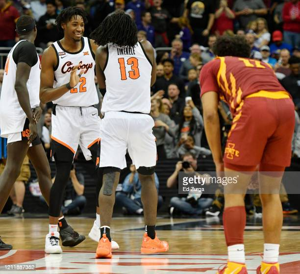 Kalib Boone and Isaac Likekele of the Oklahoma State Cowboys celebrate their 7271 win as Prentiss Nixon of the Iowa State Cyclones looks on during...