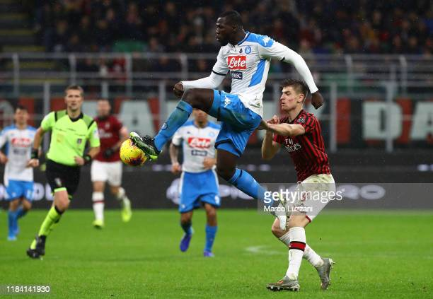 Kalidou Koulibaly of SSC Napoli is challenged by Krzysztof Piatek of AC Milan during the Serie A match between AC Milan and SSC Napoli at Stadio...