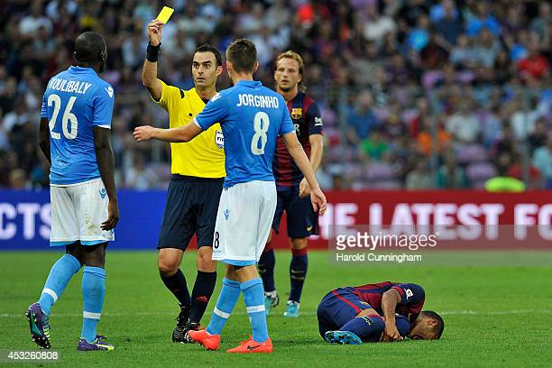 Kalidou Koulibaly of SSC Napoli receives a yellow card as Rafael Alcantara of FC Barcelona lays on the pitch in action during the preseason friendly...
