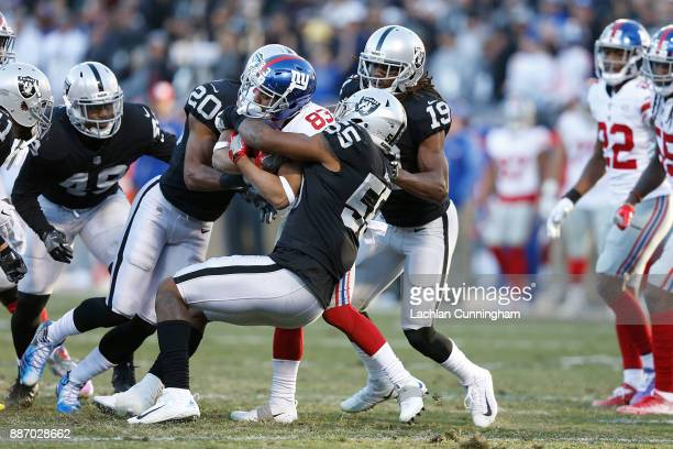 Kalif Raymond of the New York Giants is tackled by Marquel Lee and Obi Melifonwu of the Oakland Raiders at OaklandAlameda County Coliseum on December...