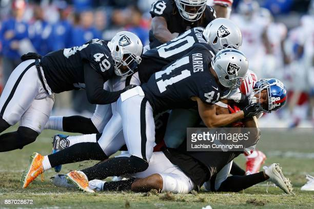 Kalif Raymond of the New York Giants is tackled by Marquel Lee Erik Harris Jamize Olawale and Obi Melifonwu of the Oakland Raiders at OaklandAlameda...