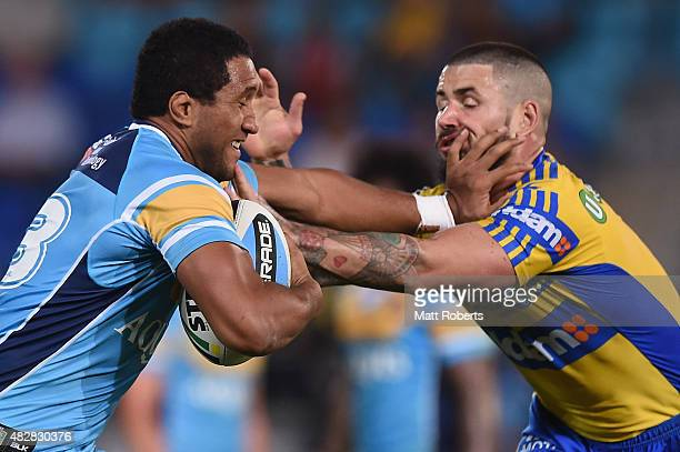 Kalifa Faifai Loa of the Titans is tackled by Nathan Peats of the Eels during the round 21 NRL match between the Gold Coast Titans and the Parramatta...