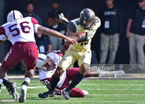 Kalija Lipscomb of the Vanderbilt Commodores avoids a tackle by Abram Jones and Adrian Portlock of the Alabama AM Bulldogs during the first half at...