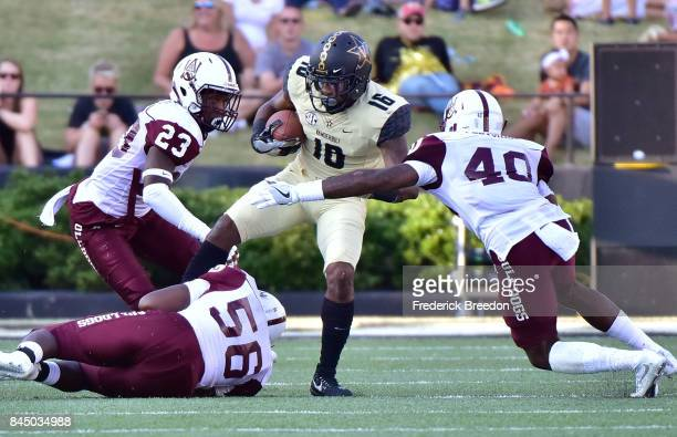 Kalija Lipscomb of the Vanderbilt Commodores is tackled by Jaylon Dorsey Abram Jones and Desmond Fletcher of the Alabama AM Bulldogs during the...