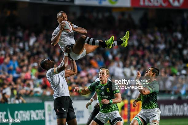 Kalione Nasoko of Fiji lifts his teammate Osea Kolinisau to the ball during the Cup Final against South Africa on the third day of the Hong Kong...