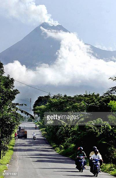Motorists travel along a highway with Mount Merapi spewing white smoke in Kaliurang 20 April 2006 Indonesia's Mount Merapi volcano showed increasing...