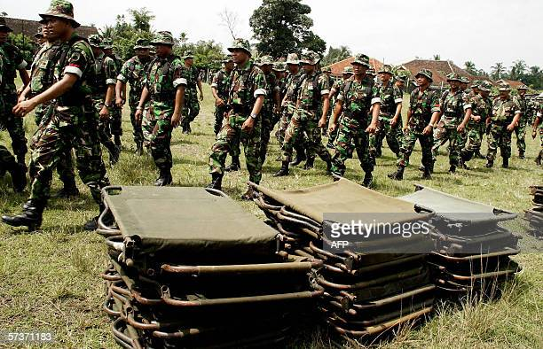 Soldiers walk past folding beds as they prepare to help in the evacuation of residents near Mount Merapi in Kaliurang 20 April 2006 Indonesia's Mount...
