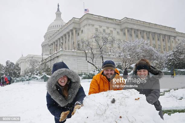 Kallie Durkit Robert Harrison and Casie Durkit roll a giant snowball while making a snow man on the grounds of the US Capitol March 21 2018 in...