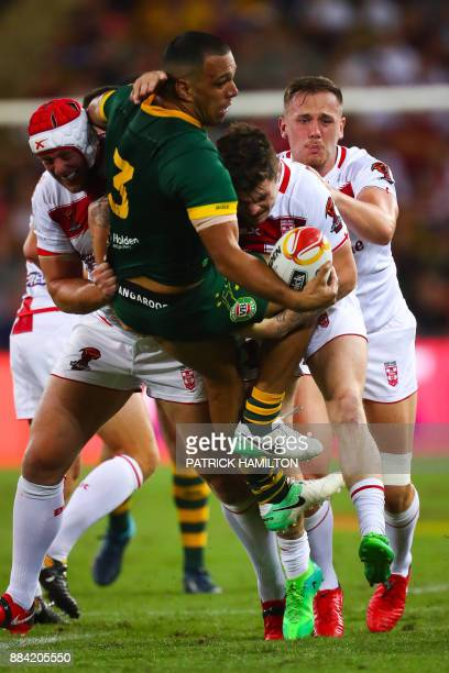 Kallum Watkins of Australia is tackled by James Roby and Chris Hill of England during the rugby league World Cup men's final match between Australia...