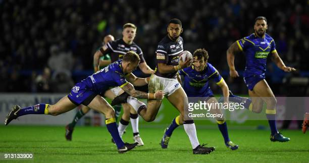 Kallum Watkins of Leeds is tackled by Kevin Brown of Warrington during the Betfred Super League match between Warrington Wolves and Leeds Rhinos on...