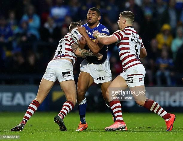 Kallum Watkins of Leeds Rhinos is tackled by George Williams and Josh Charnley of Wigan Warriors during the Round 2 match of the First Utility Super...