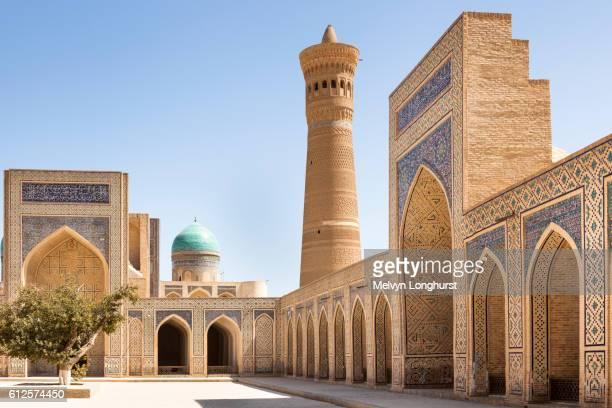 kalon mosque courtyard, also known as kalyan mosque, kalon minaret and mir i arab madrasah behind - minaret stock pictures, royalty-free photos & images