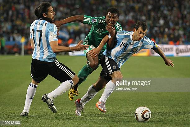 Kalu Uche of Nigeria is crowded out by Jonas Gutierrez and Javier Mascherano of Argentina during the 2010 FIFA World Cup South Africa Group B match...