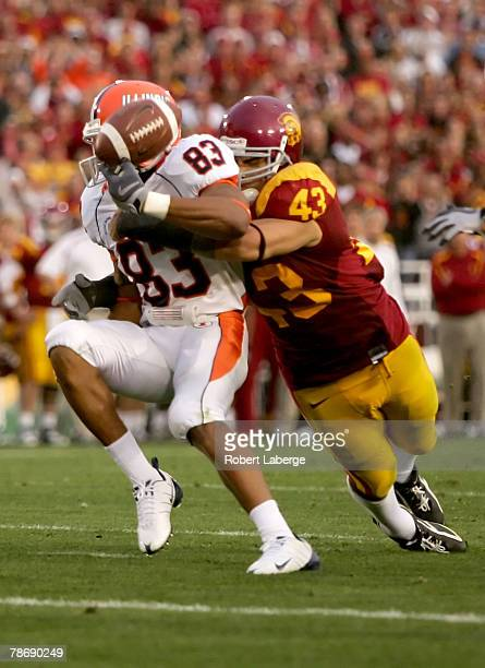 Kaluka Maiava of the USC Trojans punches the ball loose out of the hands of Jacob Willis of the Illinois Fighting Illini for a fumble in the third...