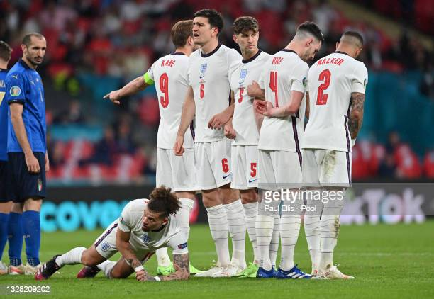 Kalvin Phillips of England lies behind the England wall as Harry Kane, Harry Maguire, John Stones, Declan Rice and Kyle Walker prepare the wall...