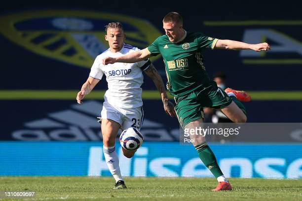 Kalvin Phillips of Leeds United battles for possession with John Lundstram of Sheffield United during the Premier League match between Leeds United...