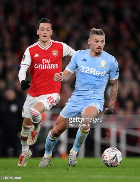 Kalvin Phillips of Leeds United makes a break past Mesut Ozil of Arsenal during the FA Cup Third Round match between Arsenal FC and Leeds United at...