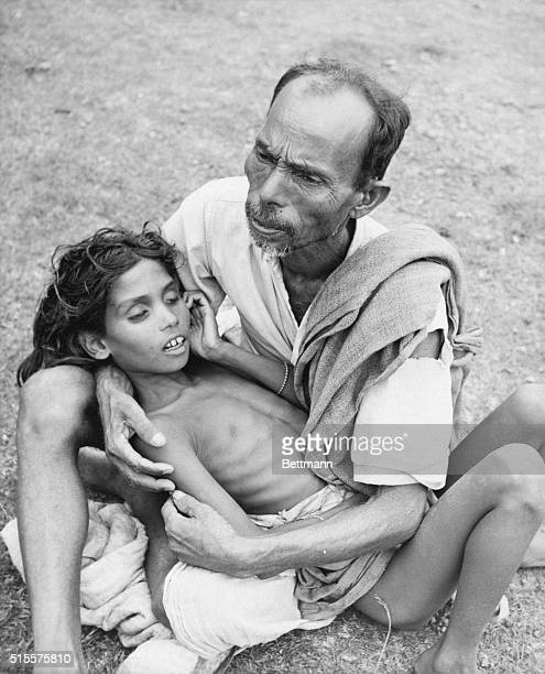east Pakistani refugee sits on hospital grounds here June 10 cradling the body of his dead son a victim of Cholera The dreaded disease has wept...