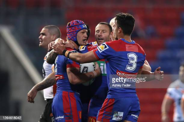 Kalyn Ponga of the Knights celebrates a try with team mates during the round 13 NRL match between the Newcastle Knights and the Wests Tigers at...
