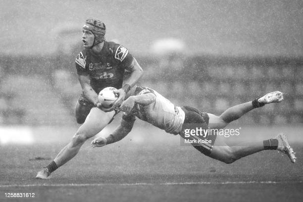 Kalyn Ponga of the Knights evades the tackle of Jake Averillo of the Bulldogs during the round 11 NRL match between the Newcastle Knights and the...