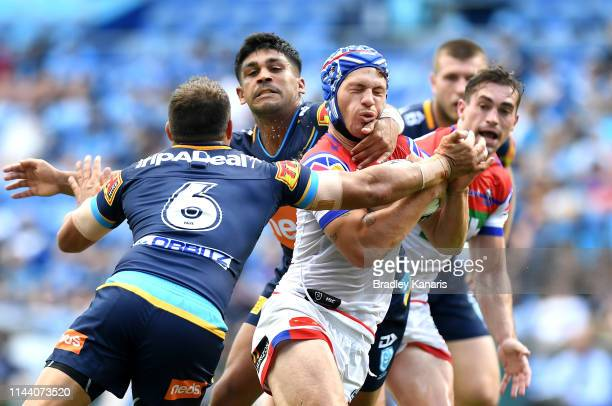 Kalyn Ponga of the Knights is caught in a high tackle during the round 6 NRL match between the Titans and the Knights at Cbus Super Stadium on April...