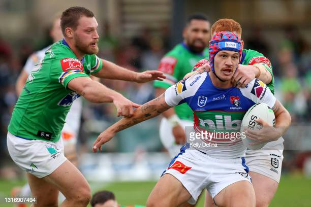 Kalyn Ponga of the Knights is tackled by Elliott Whitehead of the Raiders and Corey Horsburgh of the Raiders during the round nine NRL match between...