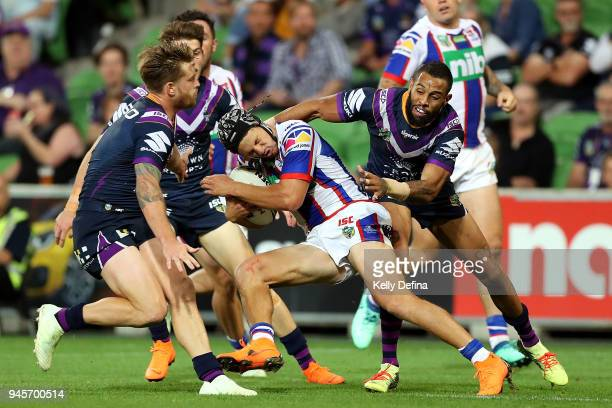 Kalyn Ponga of the Knights is tackled by the Storm defence during the round six NRL match between the Melbourne Storm and the Newcastle Knights at...