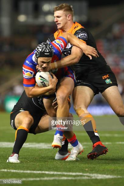 Kalyn Ponga of the Knights is tackled during the round 21 NRL match between the Newcastle Knights and the Wests Tigers at McDonald Jones Stadium on...