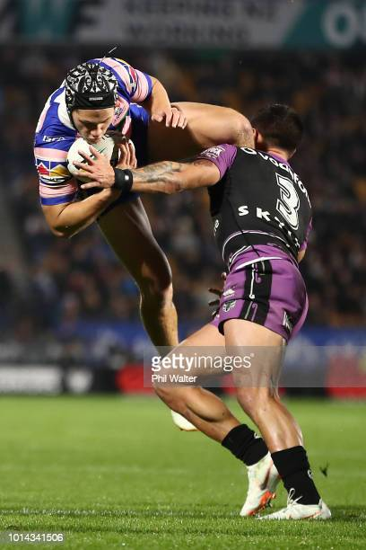 Kalyn Ponga of the Knights is tackled with this high ball by Gerard Beale of the Warriors during the round 22 NRL match between the New Zealand...