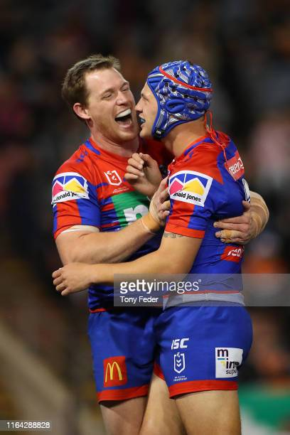 Kalyn Ponga of the Newcastle Knights celebrates a try with team mate Tim Glasby during the round 19 NRL match between the Newcastle Knights and Wests...