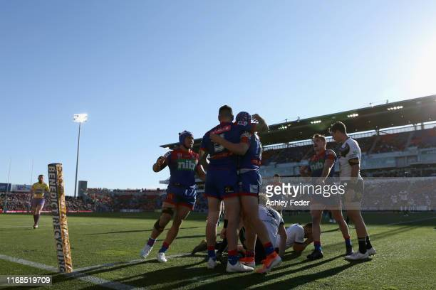 Kalyn Ponga of the Newcastle Knights celebrates his try with team mates during the round 22 NRL match between the Newcastle Knights and the North...
