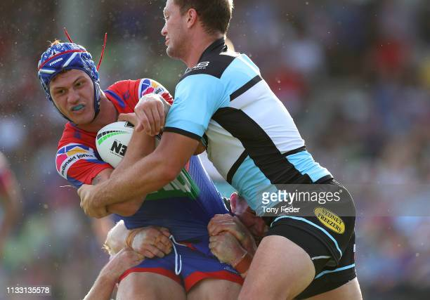 Kalyn Ponga of the Newcastle Knights is tackled by Matt Moylan of the Cronulla Sharks during the NRL Trial match between the Cronulla Sharks and the...