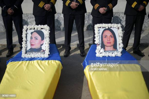 Kam Air employees stand over their colleague's coffins all Ukrainian employees of the Afghan airline at a ceremony at Kabul International Airport on...