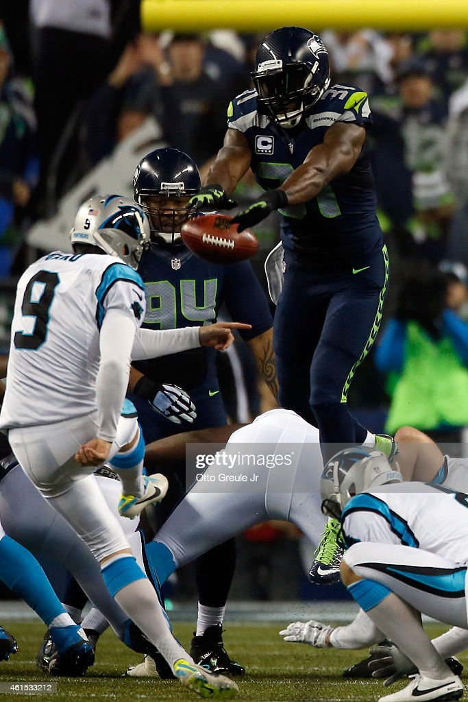 Kam Chancellor #31 of the Seattle Seahawks blocks Graham Gano #9 of the Carolina Panthers but gets called for roughing the kicker in the second quarter during the 2015 NFC Divisional Playoff game at CenturyLink Field on January 10, 2015 in Seattle, Washington.