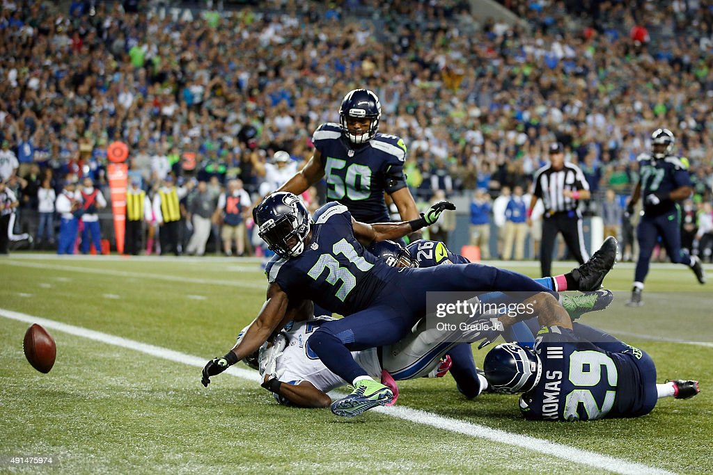 Kam Chancellor #31 of the Seattle Seahawks forces Calvin Johnson #81 of the Detroit Lions to fumble the ball near the goal line during the fourth quarter of their game at CenturyLink Field on October 5, 2015 in Seattle, Washington.