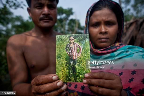 Kamal Hosen and Rahima Khartoum hold a photograph of their son 14 year old trafficking victim Din Mohammad July 4 2015 in Shamlapur Bangladesh 3...