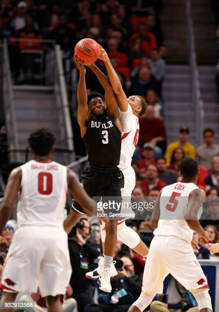 Kamar Baldwin of the Butler Bulldogs and F Daniel Gafford of the Arkansas Razorbacks reach for a rebound during the NCAA Division I Men's Basketball...