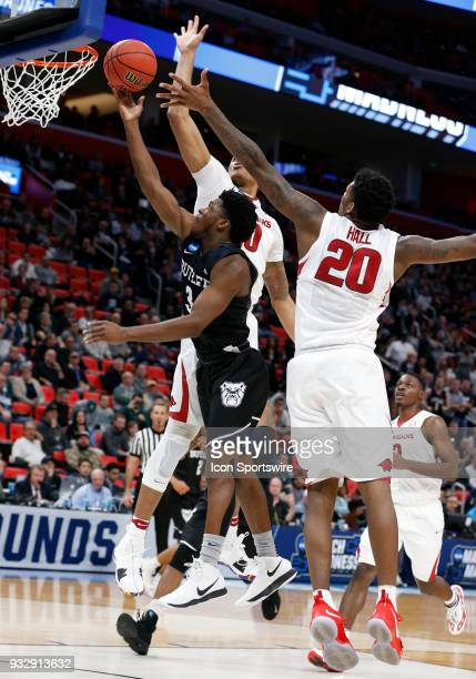 Kamar Baldwin of the Butler Bulldogs goes up for a shot between F Daniel Gafford of the Arkansas Razorbacks and F Darious Hall of the Arkansas...